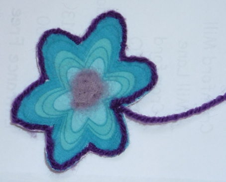 Flower outlined in acrylic yarn.